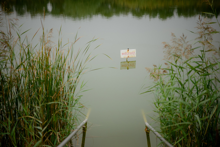 deep water sign in a lake in wedding ceremony by the lake in Nádas Resting and Adventure Park in Budapest
