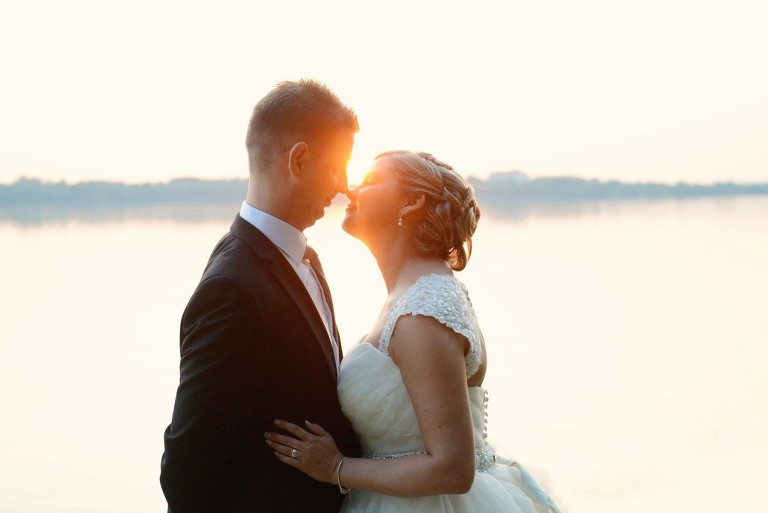 bride and groom kissing by the sunset at a lake