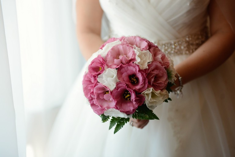 bride is holding a pink wedding bouquet