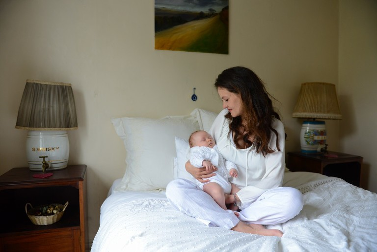 mother holding her baby in a bedroom