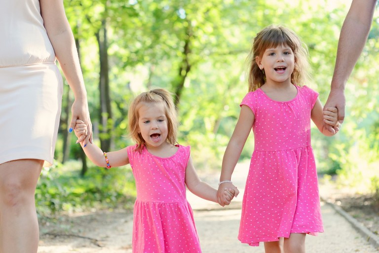 two girls in pink dresses walking in the park holding hands