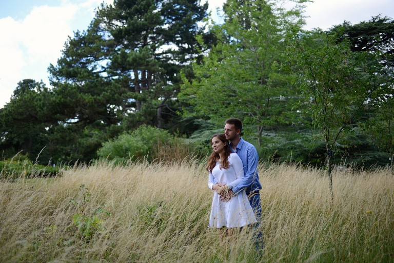sweet couple in a park with long grass, engagement photography in Cambridge