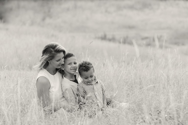 family photography with mother and two sons in a park with long grass in Wimbledon