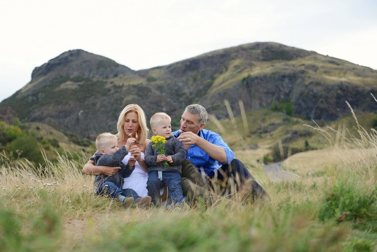 Portrait of family sitting on the grass by Athur's Seat in EDINBURGH