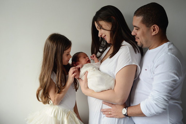 family of four looking at a newborn baby, family photography in Wimbledon