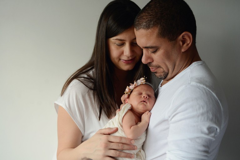 father and mother holding their newborn baby, family photography in Wimbledon