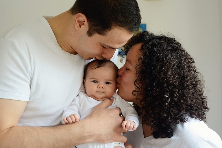 mother and father kissing their baby girl, family photography in Battersea London