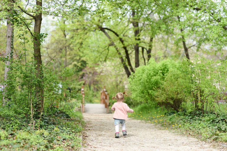 little toddler in pink jumper walking in a park among big trees