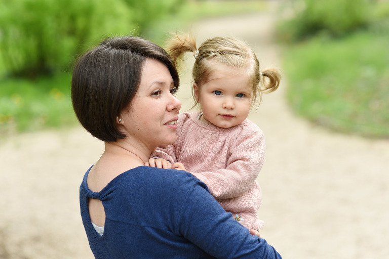 mother holding her blond toddler daughter in pink top